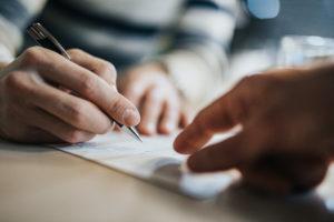 Zbliżenie na mężczyznę podpisującego umowę, podczas gdy doradca finansowy celuje w miejsce, które musi podpisać.