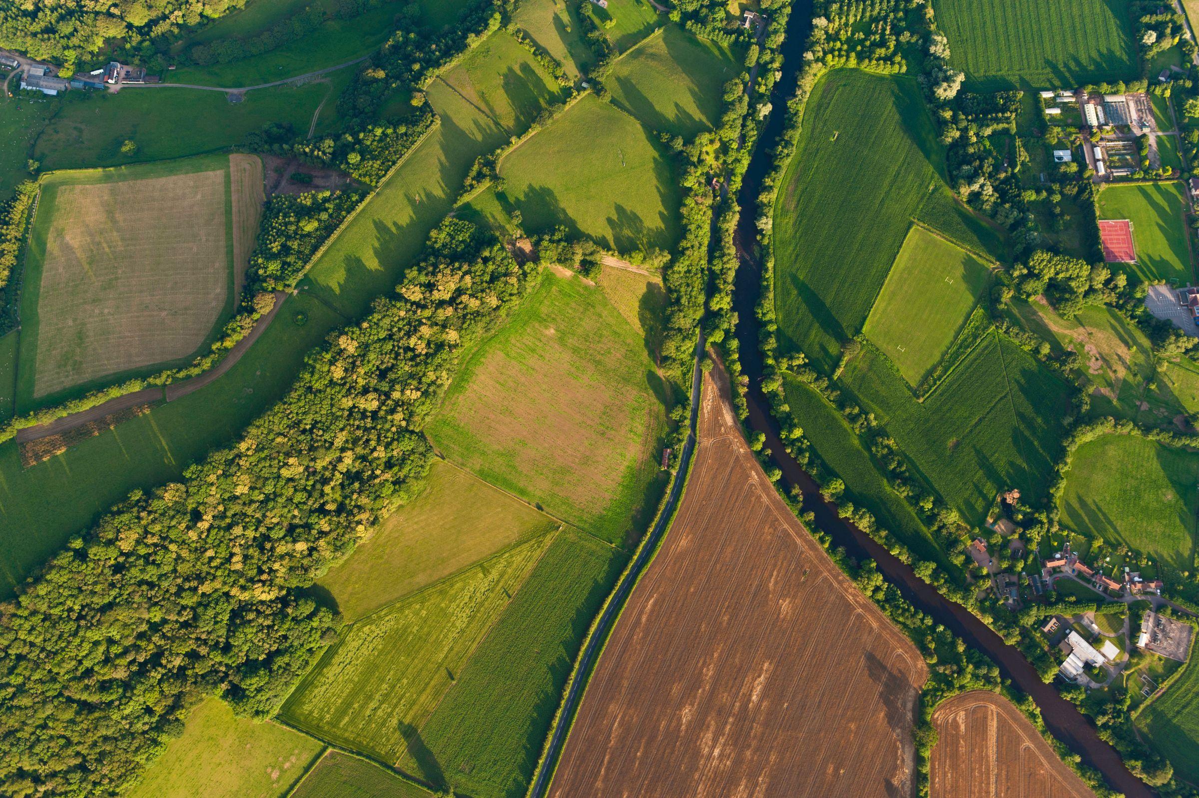 Tętniące życiem zielone uprawy, zaorane pola i pastwiska, żywopłoty i lasy otaczające farmy i wiejskie domy obok idyllicznego wiejskiego krajobrazu z góry.