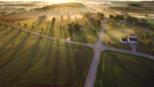 Magiczny wschód słońca przez przyziemną mgłę z długimi cieniami i promieniami słońca.