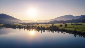 Zdjęcie przedstawia piękny zielony krajobraz, z jeziorem otoczonym drzewami i łąkami